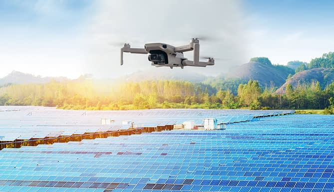 Drone sobrevoando painéis de energia solar em terreno plano