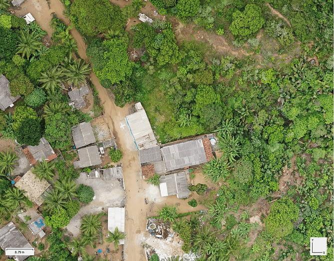 Ortomosaico de um terreno com vegetação e alguns barracos. Imagem capturada por drone