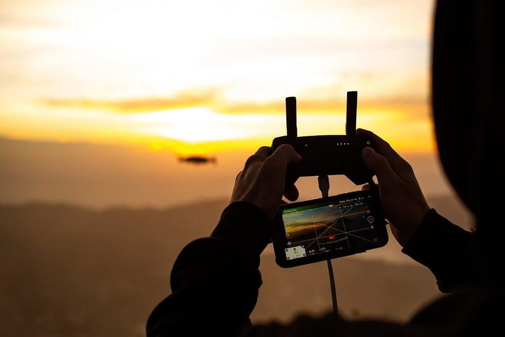 Pessoa controlando drone por controle remoto e câmera